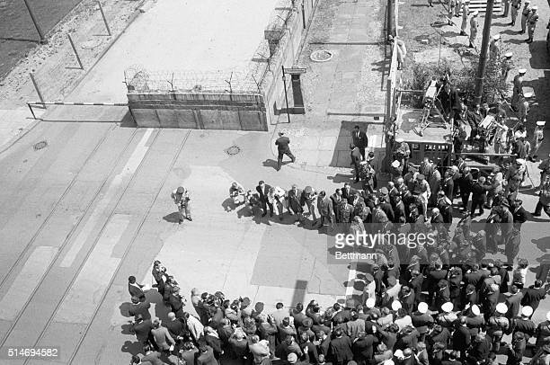 President John F Kennedy stands among reporters and onlookers on Friedrichstrasse in West Berlin where he observes the Berlin Wall It was on this day...
