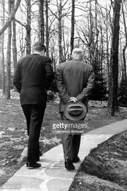 President John F Kennedy walks along a stone pathway with former President Dwight Eisenhower while contemplating the issue of the Bay of Pigs...