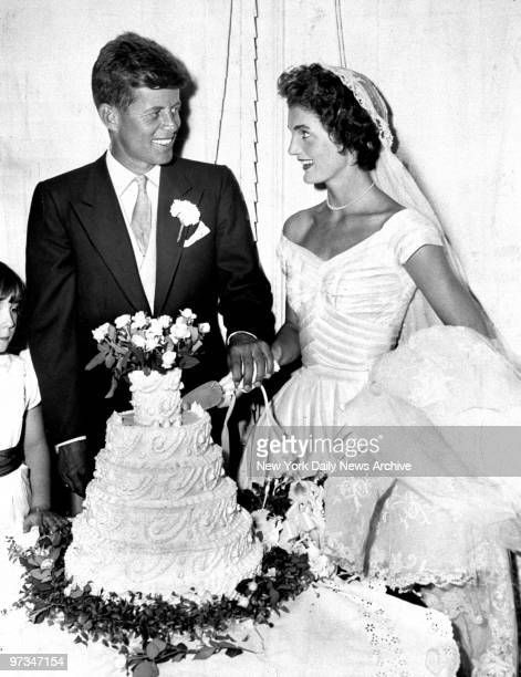 President John F Kennedy with wife Jacqueline cut the cake at their wedding in Newport Rhode Island