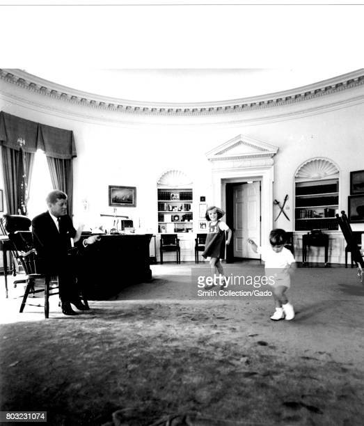 US President John F Kennedy works in the Oval Office of the White House while children John Kennedy Jr and Caroline Kennedy play October 10 1962...