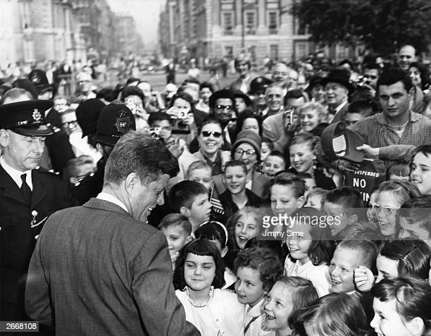 President John Kennedy surrounded by American schoolchildren as he arrives at the American Embassy in Grosvenor Square London after visits to Paris...