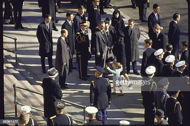 President Johnson and Lady Bird Johnson greet Jacqueline Kennedy with John Jr and Caroline outside St Mathews Cathedral before the start of requiem...