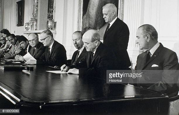 President Johnson looks on as Secretary of State Dean Rusk signs the treaty for the NonProliferation of Nuclear Weapons