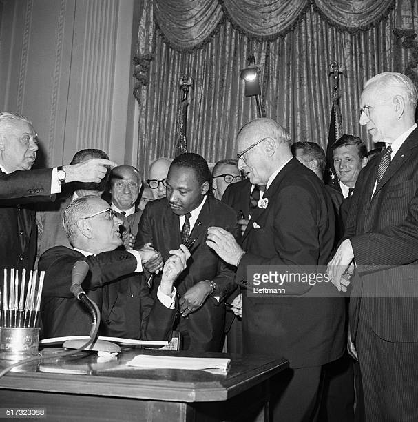 President Johnson shakes hands with civil rights leader Martin Luther King Jr and hands him a pen to sign the Civil Right Act on July 2 1964