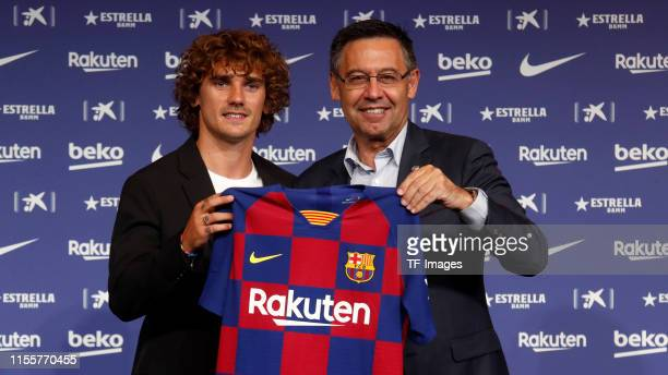 President Josep Maria Bartomeu of FC Barcelona and Antoine Griezmann of FC Barcelona present Griezmann's jersey during the press conference of FC...