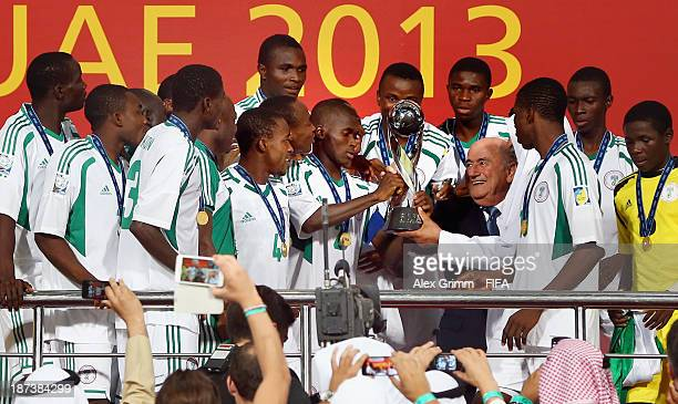 President Joseph S Blatter hands over the trophy to team captain Musa Muhammed of Nigeria after the FIFA U17 World Cup UAE 2013 Final between Nigeria...