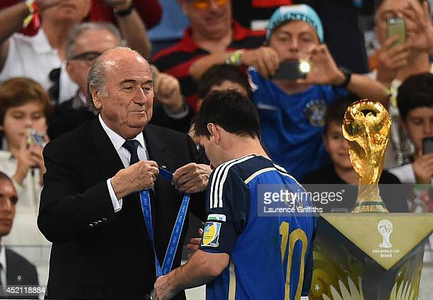 President Joseph S Blatter presents Lionel Messi of Argentina with his second place medal after being defeated by Germany 10 in extra time during the...