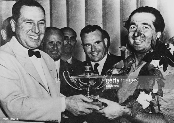President Juan Peron of Argentina handing the winners trophy to racing driver Alberto Ascari after the Argentine Grand Prix, January 18th 1953.