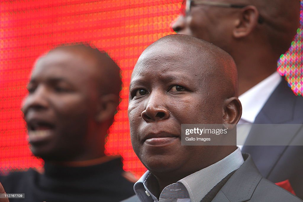 ANCYL president Julius Malema is flanked by ANC members outside the high court on April 20, 2011 in Johannesburg, South Africa. NCYL President Julius Malema is appearing on charges of hate speech for singing the song 'Shoot The Boer' laid against him by Tshwane-based lobby group AfriForum.