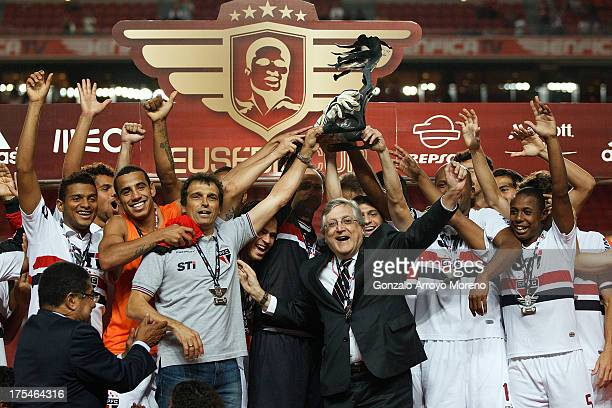 President Juvenal Juvencio of Sao Paulo FC celebrates winning the Eusebio Cup as their players hold the trophy and Eusebio claps for them during the...