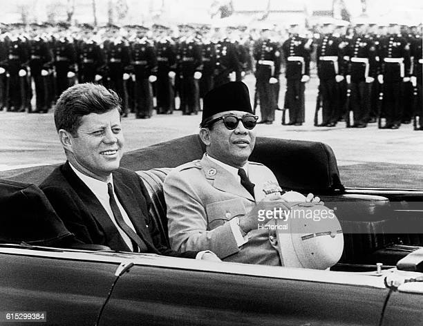 President Kennedy and Indonesia's President Sukarno riding in an open car past a row of soldiers