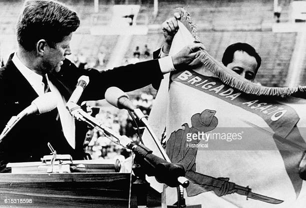 """President Kennedy displays the combat flag of the Cuban landing brigade, and declares to an audience of 40,000 that it """"will be returned this brigade..."""