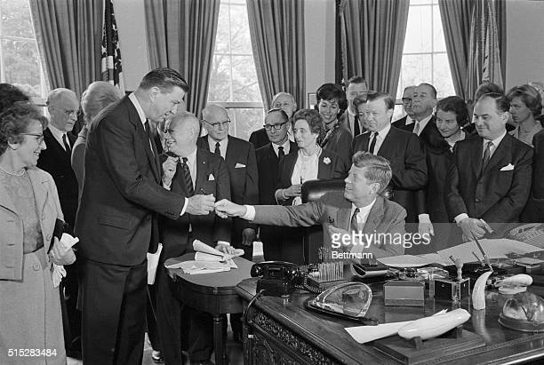 President Kennedy gives one of the pens he used to sign a bill granting a charter to the Eleanor Roosevelt Foundation to Assistant Secretary of...
