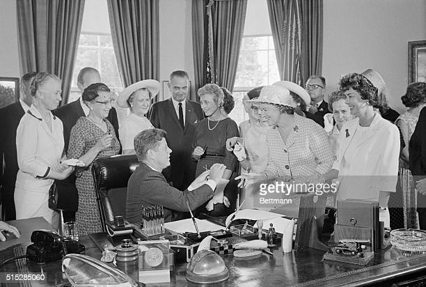 President Kennedy hands out pens during a ceremony at the White House today in which he signed into law a bill aimed at assuring women of paychecks...