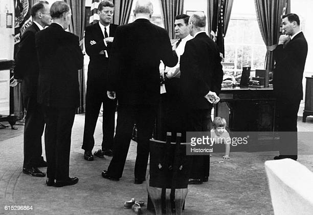 President Kennedy meets with advisors in the Oval Office while his son John Jr plays under the desk October 14 1963