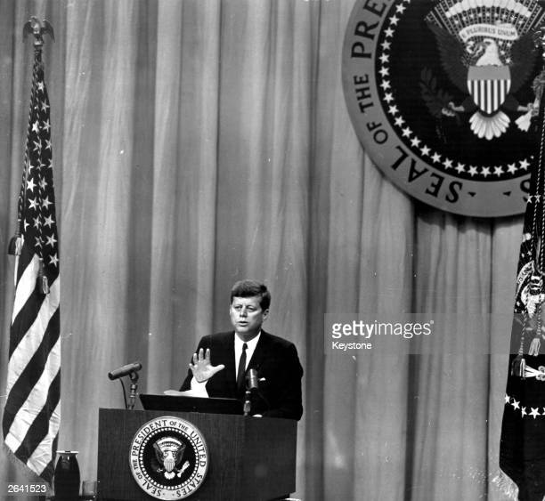 President Kennedy promises to talk about the Berlin question at a press conference in Washington The Presidential seal is displayed above him...