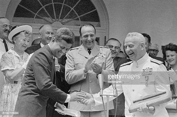 President Kennedy shakes hands with Chief of Naval Operations Arleigh Burke after presenting him with the Distinguished Service Medal at his...