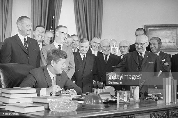 President Kennedy signs into law a $600-billion measure to aid Latin America. Present at the signing are : Vice President Lyndon B. Johnson,...