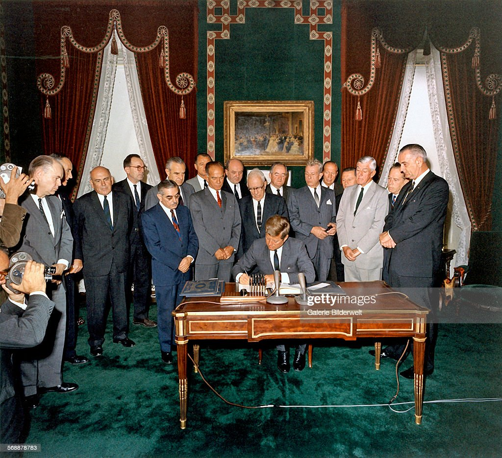 President Kennedy signs the Limited Nuclear Test Ban Treaty in the Treaty Room at the White House. 7th October 1963. Left to Right: William Hopkins, Senator Mike Mansfield, John J. McCloy, Adrian S. Fisher, Senator John Pastore, W. Averell Harriman, Senator George Smathers, Senator J.W. Fulbright, Secretary of State Dean Rusk, Senator George Aiken, President Kennedy, Senator Hubert H. Humphrey, Senator Everett Dirksen, William C. Foster, Senator Howard W. Cannon, Senator Leverett Saltonstall, Senator Thomas H. Kuchel, Vice President Johnson. Photo: Robert Knudsen, White House. Washington D