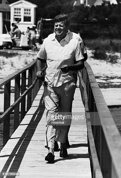 President Kennedy walking across a bridge while on vacation at Hyannisport Massachusetts