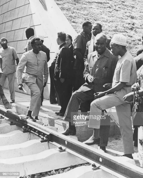 President Kenneth Kaunda of Zambia and President Julius Nyerere of Tanzania rest their feet on the sleepers of the new Great Uhuru Railway which...