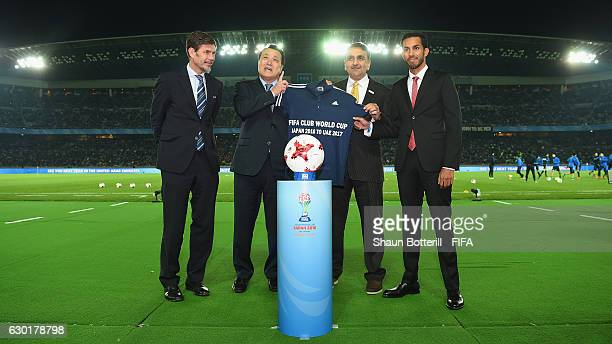President Kohzo Tashima hands over a shirt to Aref Al Awani of LOC UAE as Zvonimir Bodan looks on during the FIFA Club World Cup final match between...