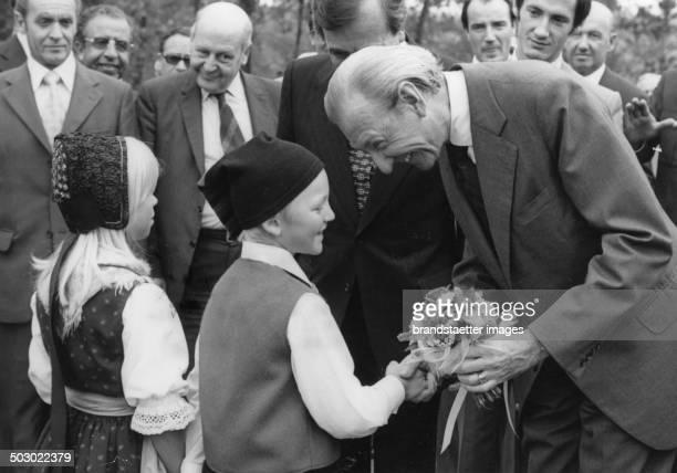 President Kurt Waldheim receives flowers from schoolchildren in Austria circa 1990