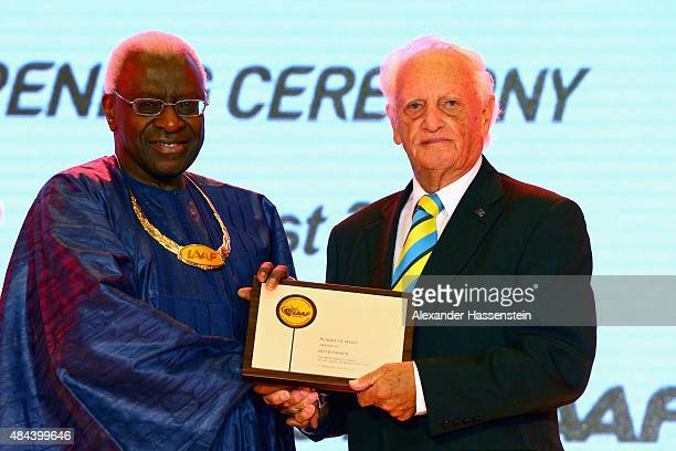 President Lamine Diack hand sover the Plaque of Merit to Keith Parker during the IAAF Congress Opening Ceremony at the Great Hall of the People at...