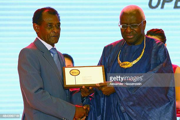 President Lamine Diack hand sover the Plaque of Merit to Vivian Gungaram during the IAAF Congress Opening Ceremony at the Great Hall of the People at...