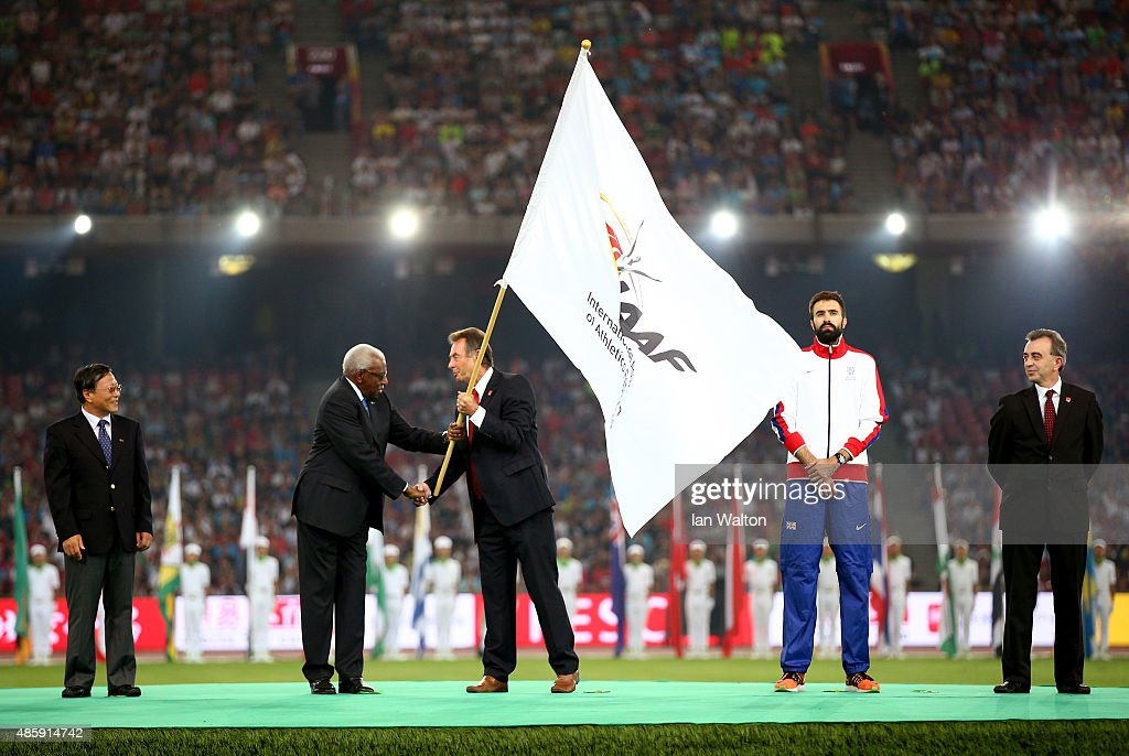 President Lamine Diack hands over the IAAF flag to President of UK athletics Lynn Davies during the closing ceremony during day nine of the 15th IAAF World Athletics Championships Beijing 2015 at Beijing National Stadium on August 30, 2015 in Beijing, China.