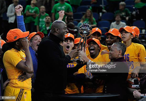 President Lisa Borders hands the Championship Trophy to Magic Johnson owner of the Los Angeles Sparks after a win in Game Five of the 2016 WNBA...