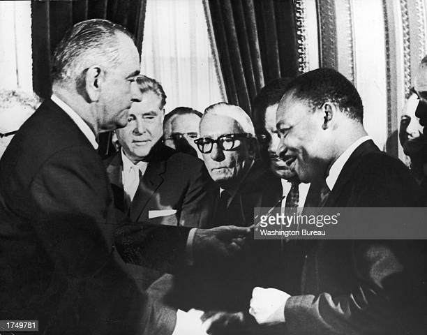 US President Lyndon B Johnson hands a pen to civil rights leader Rev Martin Luther King Jr during the the signing of the voting rights act as...
