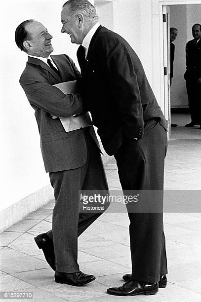 President Lyndon B. Johnson leans over a political colleague in mock intimidation to parody how he gets his way in Washington.