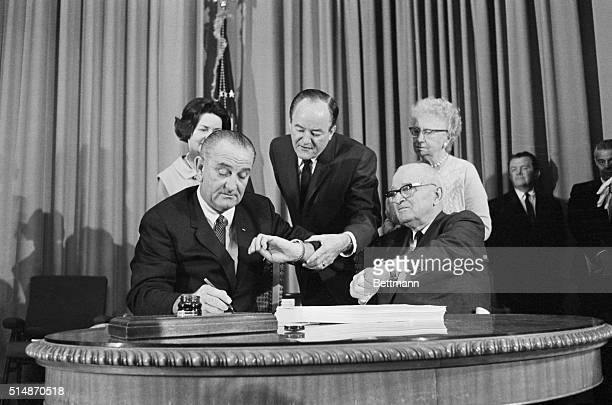 President Lyndon B. Johnson signs the Medicare bill as Vice President Humphrey and Harry S. Truman both check the time.