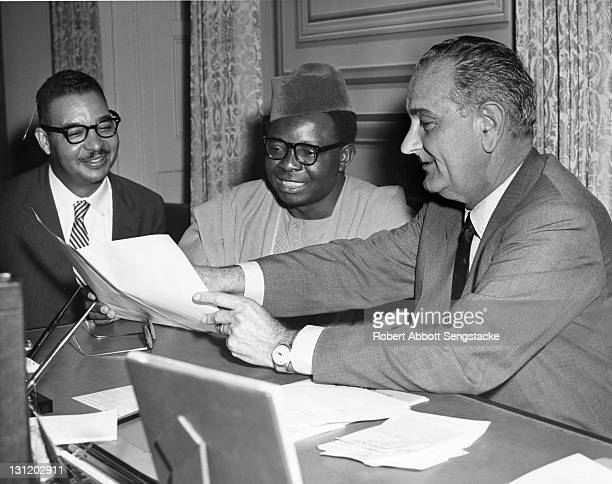 US President Lyndon Baines Johnson shows a document to Somalia Prime Minister Muhammad Ibrahim Egal as American journalist Louis E Martin watches...