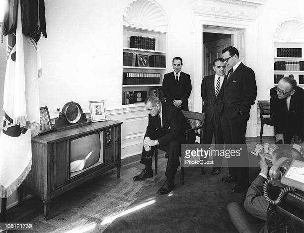 President Lyndon Johnson and various staff members watch the Saturn rocket launch on a television in the White House's Oval Office, Washington DC,...