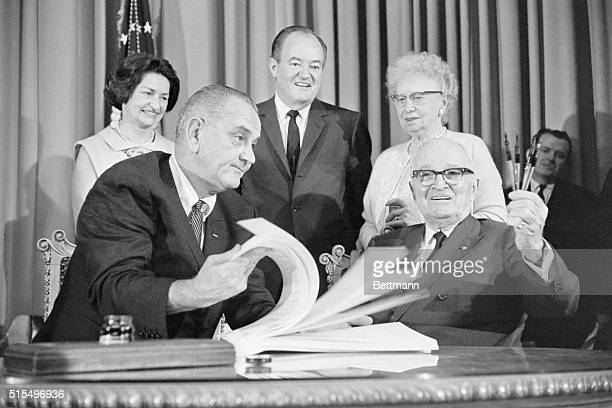 President Lyndon Johnson flips through the pages of the medicare bill so former President Harry Truman can see it but Truman seems to be too busy...