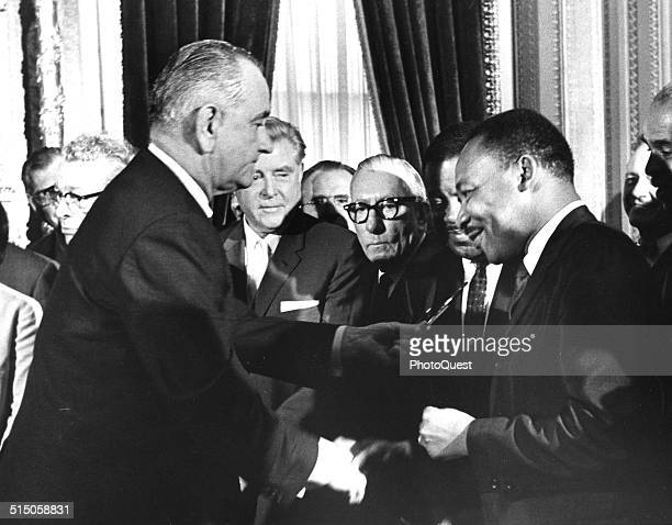 President Lyndon Johnson hands a souvenir pen to the Reverend Martin Luther King Jr after signing the Voting Rights Bill at the US Capital,...