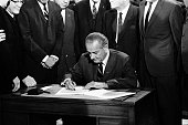 President lyndon johnson signs the civil rights bill while seated at picture id459212795?s=170x170