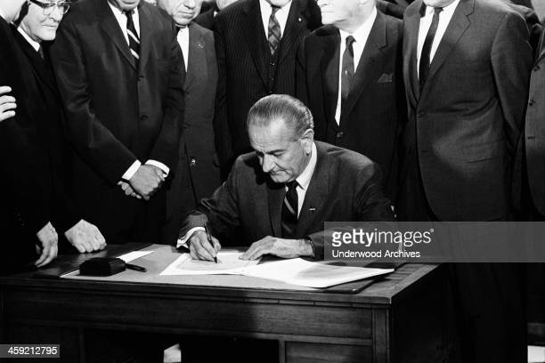 President Lyndon Johnson signs the Civil Rights bill while seated at a table surrounded by members of Congress Washington DC April 11 1968