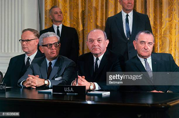 President Lyndon Johnson sitting with Arthur Goldberg and Dean Rusk during White House ceremony in which a treaty was signed barring nuclear weapons...