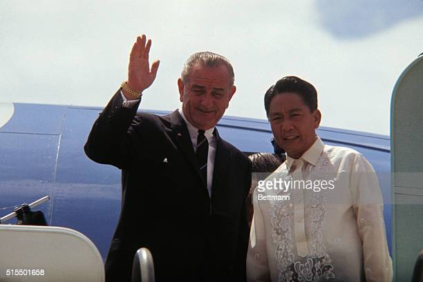 President Lyndon Johnson standing with President Ferdinand Marcos at plane entrance waves goodbye October 27th prior to departure from Manila Airport