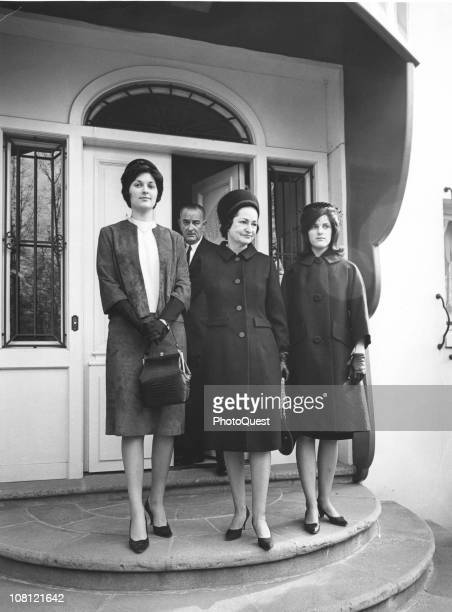 US President Lyndon Johnson steps through a door as First Lady Lady Bird Johnson and their daughters Lynda and Luci stand together November 28 1963