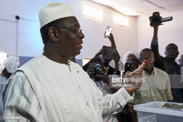 President Macky Sall looks at his finger with electoral ink on it after casting his vote at a polling station on February 24 2019 in Fatick Senegal...