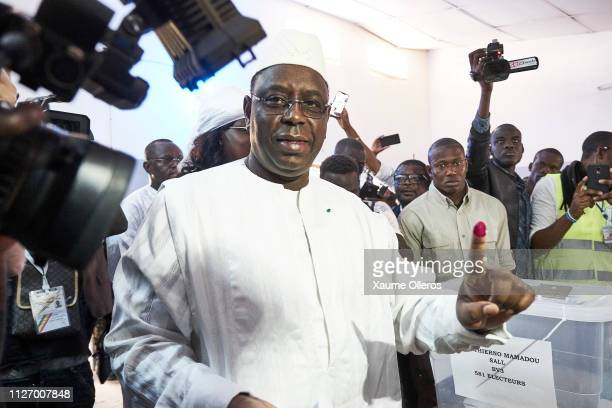 President Macky Sall shows his finger covered with electoral ink after casting his vote at a polling station on February 24 2019 in Fatick Senegal 67...