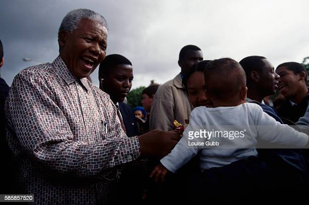 President Mandela bursts with laughter as a baby refuses his lollipop during Creche visit Former President of South Africa and longtime political...