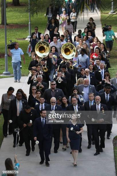 President Mark B Rosenberg leads a procession of friends family Florida International faculty and students as they mourn together during a vigil for...