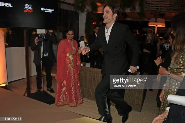 President Meher Tatna and Robert Pattinson at Nikki Beach for the HFPA Participant Media event honoring Help Refugees on May 19 2019 in Cannes France