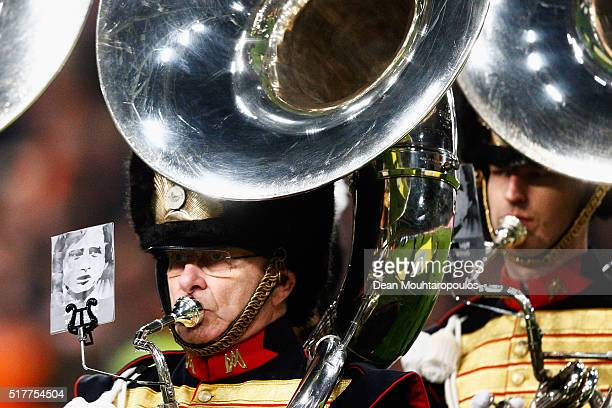 President, Michael van Praag plays a Sousaphone along with other members of a marching band with pictures on their music books of deceased legendary...
