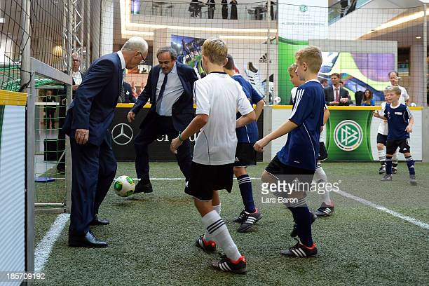 UEFA president Michel Platini and former German national player Franz Beckenbauer play football with children prior to the DFB Bundestag at the NCC...